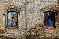 Gammal tegelstenvägg med fönster av övergiven byggnad Grungebakgrund av åldrig stenyttersida Arkivbilder