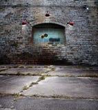 Gammal tegelstenvägg med fönstret för glass kvarter Fotografering för Bildbyråer