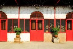 Gammal tegelstenvägg med röda dörrar och fönster och två krukväxter Arkivbilder