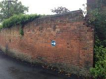 Gammal tegelstenvägg med vägmärket Arkivfoto