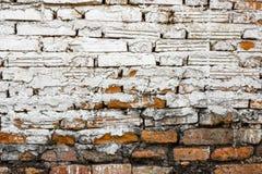 Gammal tegelstenvägg med vit-röd bakgrund och grov konstruktion arkivfoton