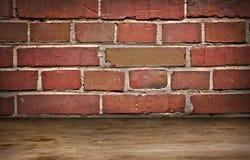 Gammal tegelstenvägg och träflor arkivfoto
