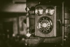 Gammal telefon för tappningväggmontering med mässingsklockor i monokromt - retro fotografi royaltyfri bild