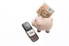 Gammal telefon och piggi-bank med pengar Royaltyfria Bilder