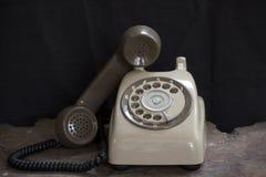 Gammal telefon på en tabell, roterande diskett på trätabellgrungebakgrund Arkivbilder
