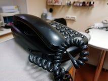 Gammal telefon på tabellen med tilltrasslad telefonkabel royaltyfri bild