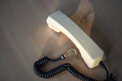 Gammal telefonlur med en sönderriven tråd på ett kontorsskrivbord arkivbild