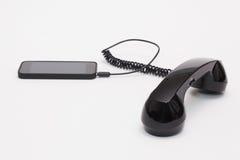 Gammal telefonmottagare och kabelanslutning med den nya telefonen Royaltyfria Foton