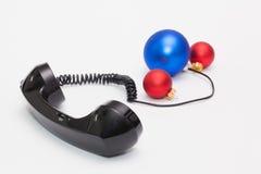 Gammal telefonmottagare och kabelanslutning med julgarnering Arkivfoto