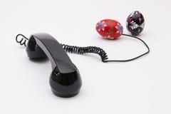 Gammal telefonmottagare och kabelanslutning med påskägg Arkivfoton