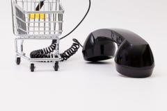 Gammal telefonmottagare och kabelanslutning med shoppingspårvagnen Arkivbilder
