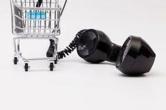 Gammal telefonmottagare och kabelanslutning med shoppingspårvagnen Arkivfoton