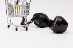 Gammal telefonmottagare och kabelanslutning med shoppingspårvagnen Royaltyfri Foto