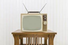 Gammal television med antennen på den Wood tabellen Arkivbild