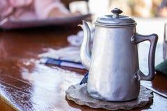Gammal tenn- te- eller kaffekruka på trätabellen Arkivbilder