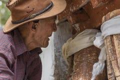Gammal tibetan man som kontrollerar forntida träbönhjul Royaltyfria Foton