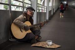 Gammal tiggarelekgitarr som tigger pengar Arkivfoto