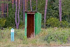 Gammal träöppen toalett i natur i grönt gräs och vegetation arkivfoto