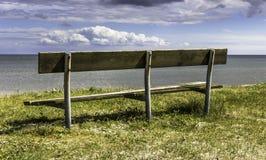 Gammal träbänk med trevlig sikt över havet royaltyfri foto