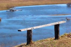 Gammal träbänk på en bank för flod` s Royaltyfri Bild