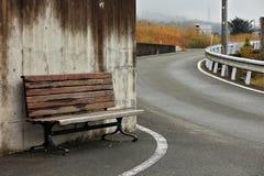 Gammal träbänk på trottoaren på vägen royaltyfri fotografi