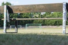 Gammal träbänk som förbiser fotbollfältet med mål royaltyfria foton