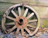 Gammal träbenägenhet för vagnhjul mot väggen royaltyfri bild