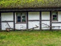 Gammal träbondgård med historiska lantbrukverktyg Fotografering för Bildbyråer
