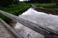 Gammal träbro över floden Royaltyfri Foto