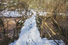 Gammal träbro över floden som täckas med snö royaltyfri fotografi