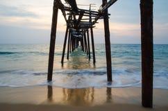 Gammal träbro i havet med solnedgång Arkivbilder