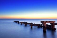 Gammal träbrygga på solnedgången arkivfoton