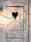 Gammal trädörr med en sniden romantisk hjärta Arkivbilder
