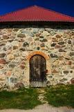 Gammal trädörr med ett lås i ett stenhus Royaltyfri Bild