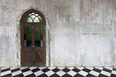 Gammal trädörr på en bakgrund för vägg för stenbetongcement Arkivfoto