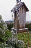 Gammal träfågelförlagematare med istappar som hänger från stolpen arkivbild