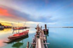 Gammal träfiskebro till havet med solnedgång Royaltyfri Fotografi