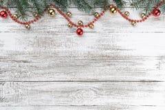Gammal träjulbakgrund Granfilialer Guld- och röda struntsaker röda girlander xmas för kortillustrationvektor Top beskådar din avs arkivbild