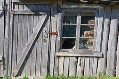 Gammal träladugård med en stängd dörr och ett brutet fönster Royaltyfri Foto