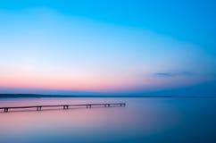 Gammal träpir på en sjö på soluppgång royaltyfri fotografi