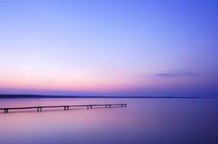 Gammal träpir på en sjö på soluppgång arkivbild