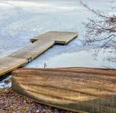 Gammal träroddbåt och pir i den djupfrysta sjön Royaltyfri Bild