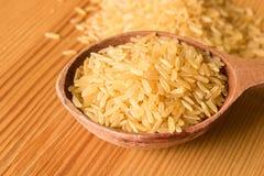 Gammal träsked med ris på en trätabell close upp Det conc arkivbilder