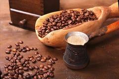 Gammal träskopa med kaffebönor, kaffekvarnen och Cezve på den mörka stentabellen arkivbild