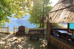Gammal träsummerhouse med bänkar på kusten av sjön Ritsa, Abchazien Arkivfoton