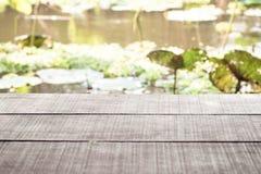 Gammal trätabell och sjön med asiatisk tropisk sjölotusblomma i bakgrund Natur ferie askfat royaltyfri fotografi