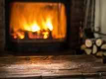 Gammal trätabell och spis med varm brand arkivfoton