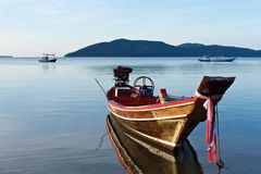 Gammal träthai traditionell fiskebåt reflekterad i vattnet arkivfoto