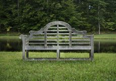 Gammal träträdgårds- bänk på ett damm fotografering för bildbyråer