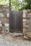Gammal träträdgårds- dörr på lutning in i trädgård med stenväggar på den Tenedos Bozcaada ön vid det Aegean havet arkivbilder